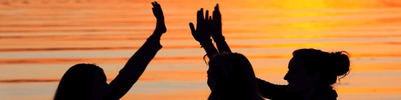 three women raising hands to clap high five