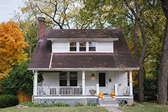 white house with gray roof; orange pumpkins on the porch